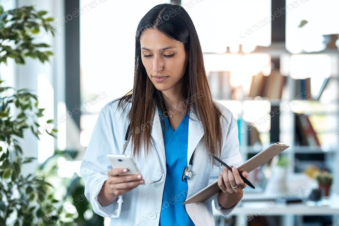 confident young female doctor using her mobile phone while holding a clipboard