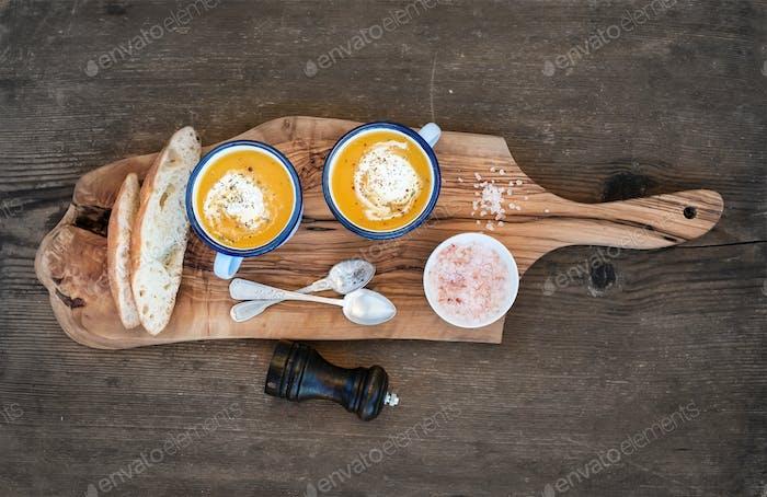 Sopa de crema de calabaza casera en tazas de esmalte con hierbas y rebanadas de pan fresco