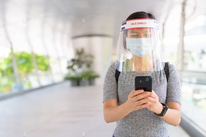 Young Asian woman using phone with mask and face shield for protection from corona virus outbreak in