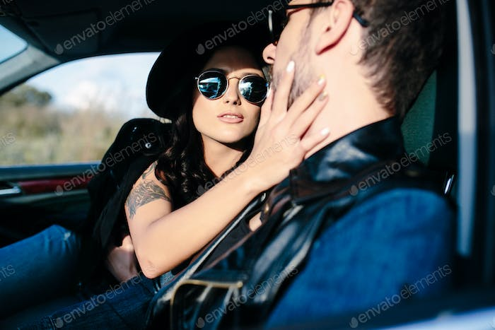 Portrait of young beautiful couple in the car