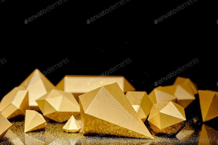 Nahaufnahme von glänzenden facettierten Goldstücken und goldenem Staub, die sich auf Schwarz spiegeln
