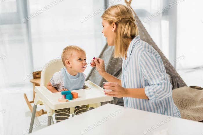 mom feeding son in highchair with baby food