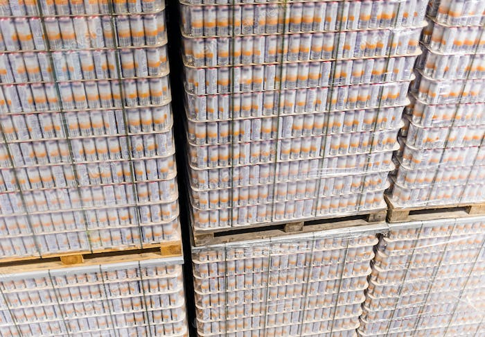 Tall stack of products on pallets in warehouse