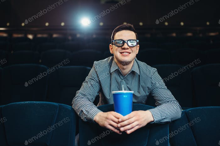 Teenager in 3d glasses holds beverage in cinema