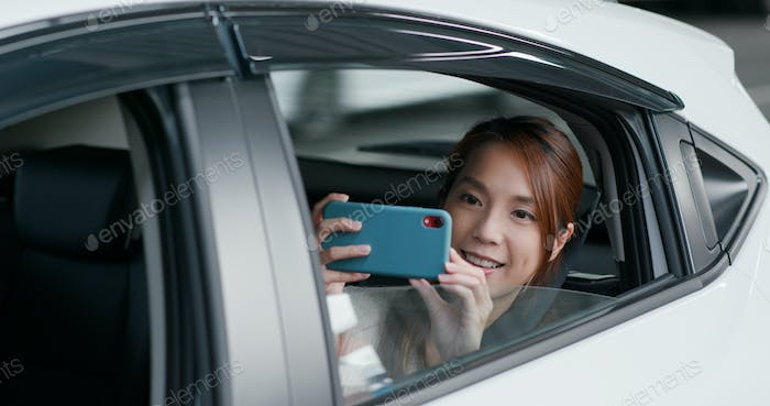 Woman uses phone to take photo in car