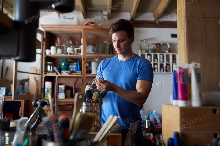 Man In Workshop Escogiendo Pincel para Upcycling y proyectos de manualidades