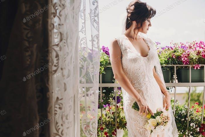 Wunderschöne Braut in erstaunlichem Kleid und mit Hochzeitsstrauß posiert auf Balkon