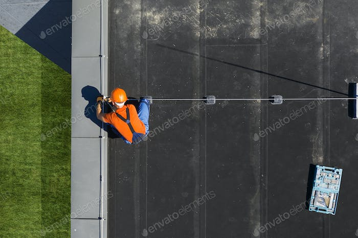 Technician Installing Lightning Protection Rod on Top of Building