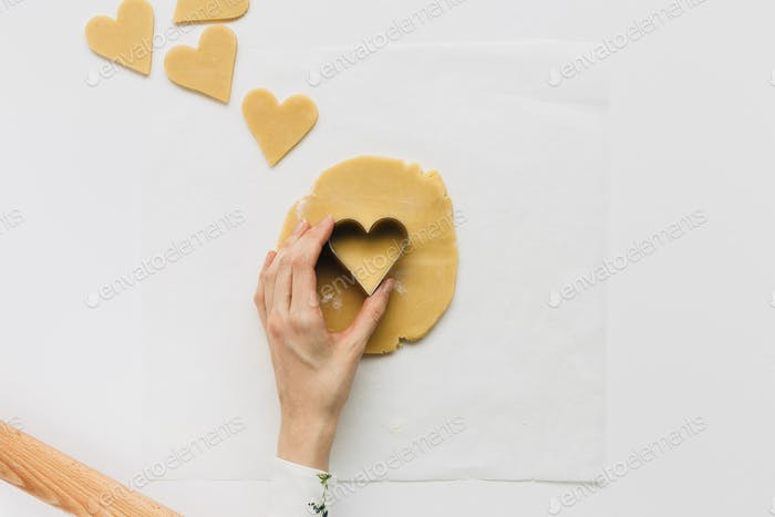Female Cutting out Heart Shaped Biscuit on White Table