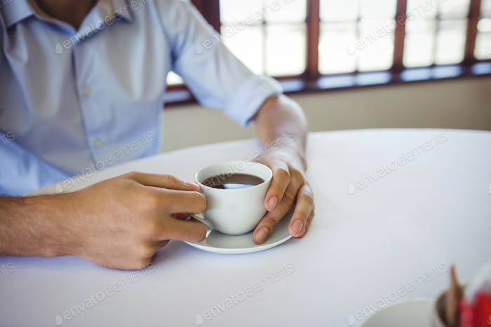 Mid section of man having coffee in restaurant