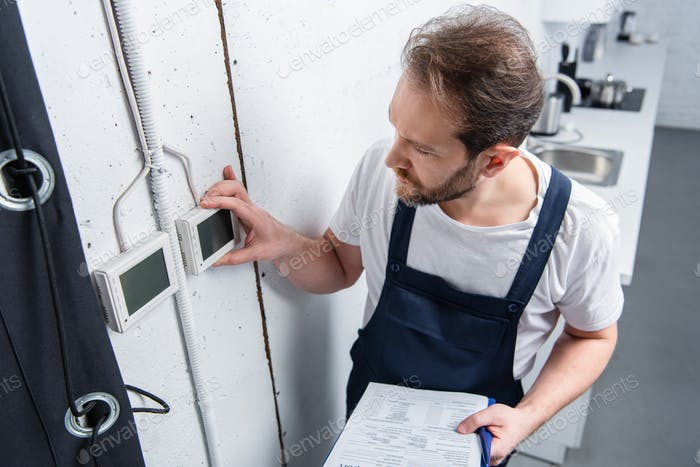 high angle view of adult electrician with clipboard checking electrical panel