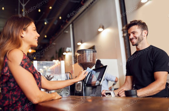 Weibliche Kunden zahlen Barista am Coffee Shop Sales Desk