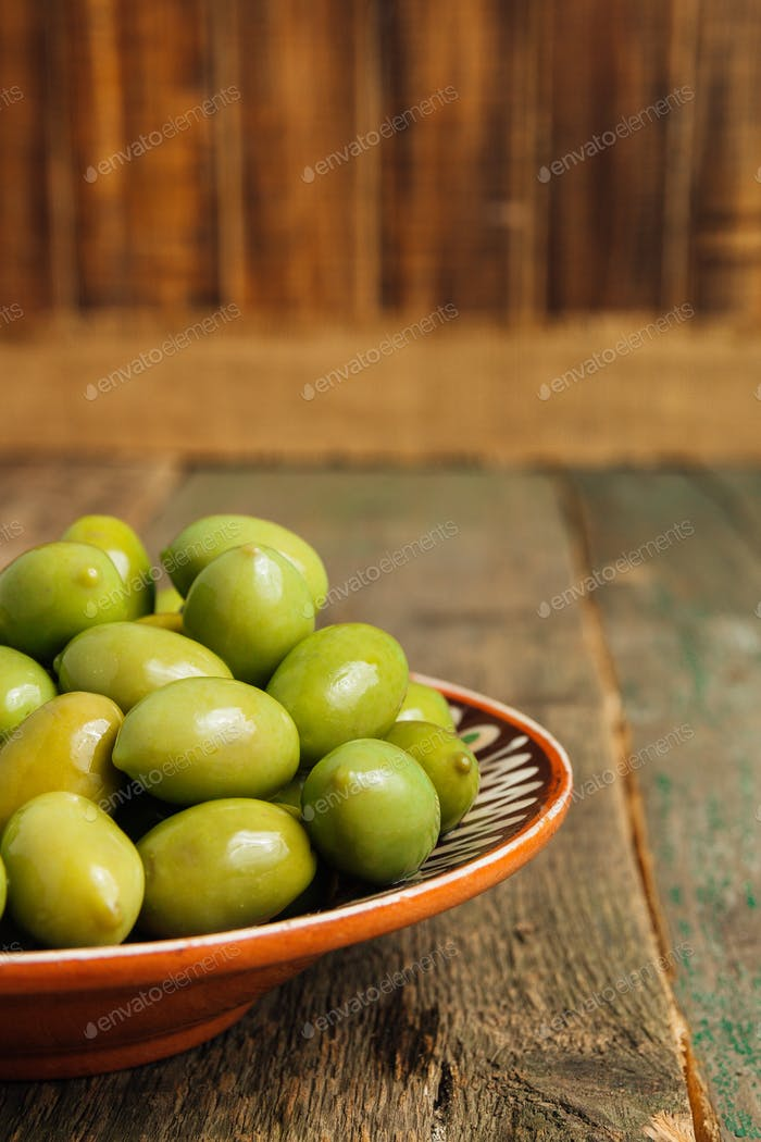 Green olives in brown bowl