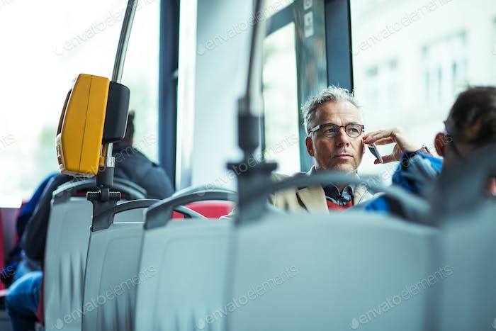 Mature businessman with smartphone travelling by bus in city.