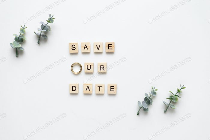 Wooden letters  spelling save our date, oregano branches and wed