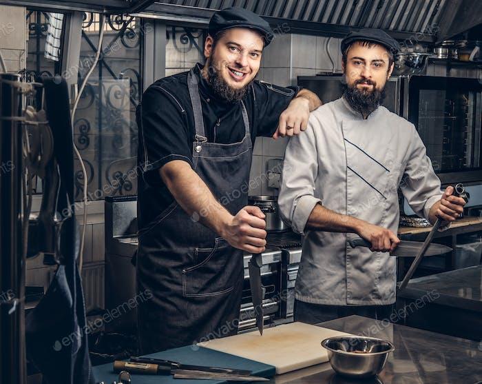 Два бородатых повара, одетые в униформу и шляпы позируют на кухне, смотрят на камеру.