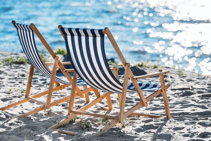tumbonas de rayas y más frescas en la playa de arena