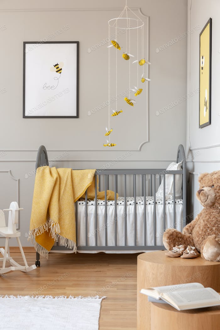 Posters on the walls of chic baby bedroom with grey and yellow d