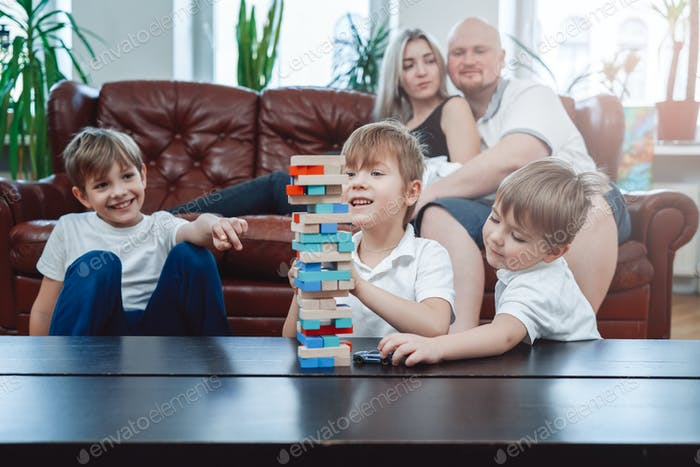 Domestic life of joyful family at home in daytime playing game