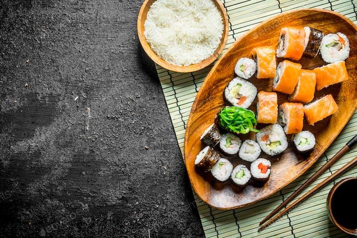 Japanische Rollen auf einem Teller mit Reis und Sojasauce.