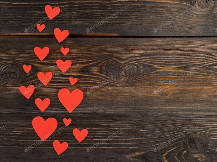 Lots of red paper hearts on a dark brown rustic weathered wooden background, top view