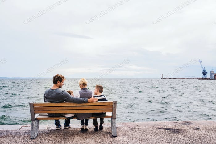 Rear view of young family with two small children on bench outdoors on beach.