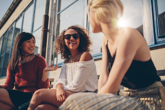 Drei junge Frauen treffen sich im Café im Freien