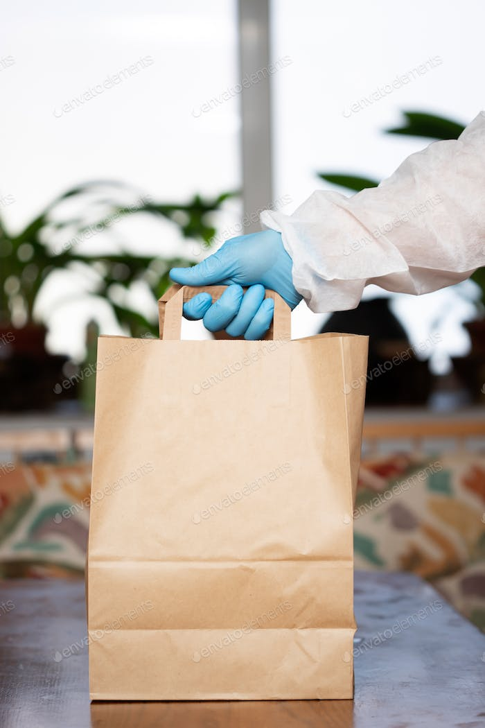 Man's hand holding bags of groceries during coronavirus pandemic. COVID-19 concept.