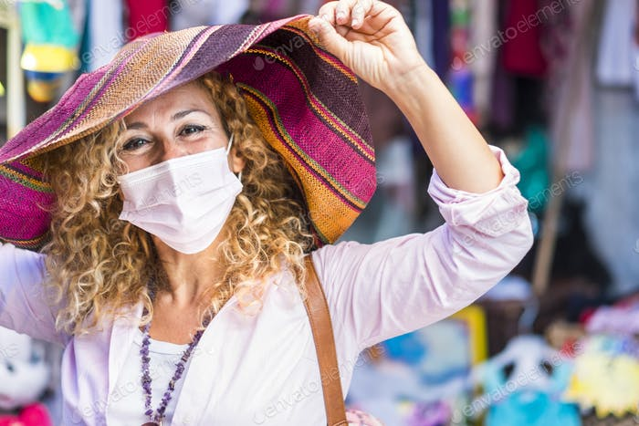 Smiling blonde and curly woman enjoying the flea market wearing a beautiful hat and face mask