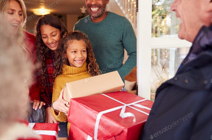 Grandparents Arriving With Gifts To Celebrate Multi-Generation Family Christmas At Home