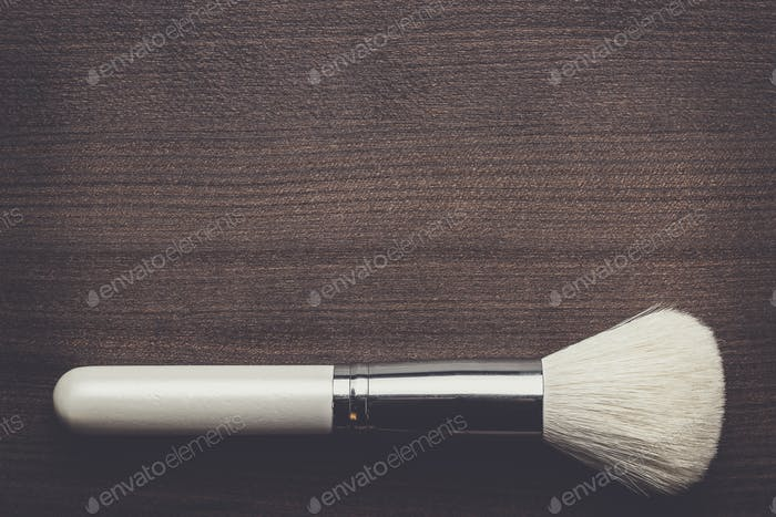 white make-up brush on wooden table