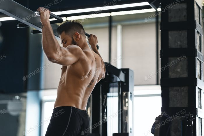 Muscular athlete pulling up on horizontal bar at gym
