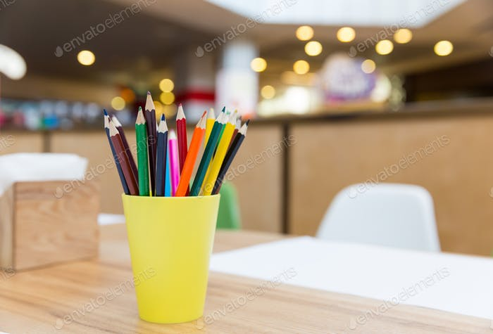 Colorful pencils in yellow glass closeup