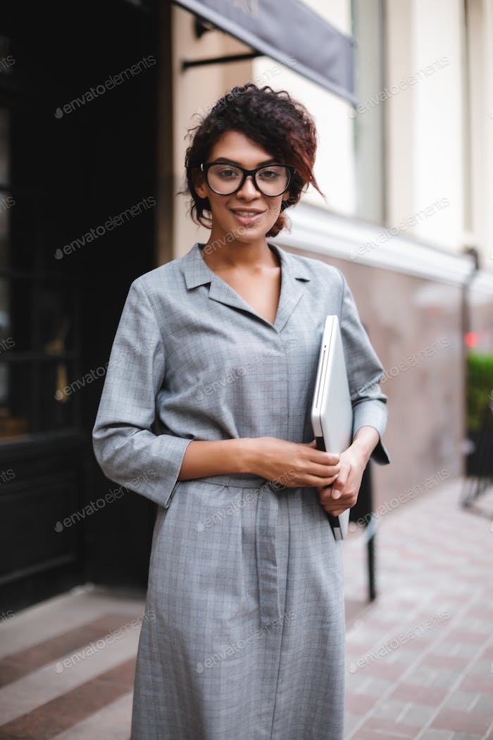 African American girl in glasses standing with laptop in hand and dreamily looking in camera