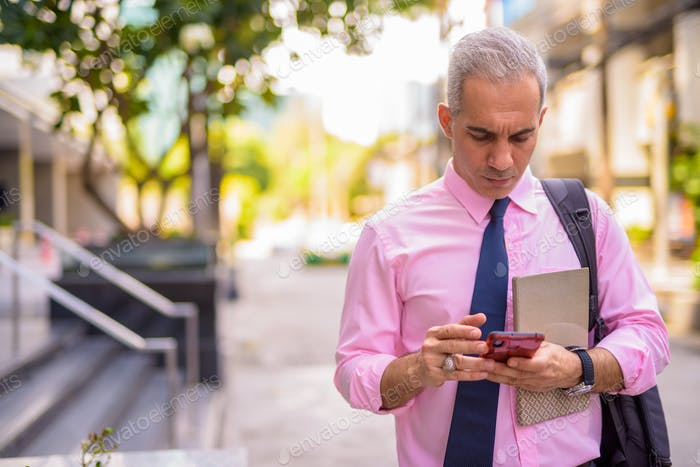 Stressed Persian businessman using phone in the city streets outdoors