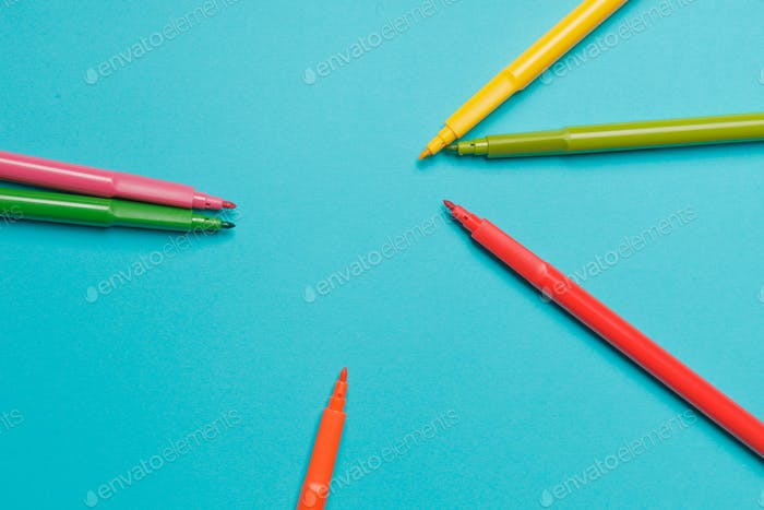 Several colored felt-tip pens on bright blue paper background close up