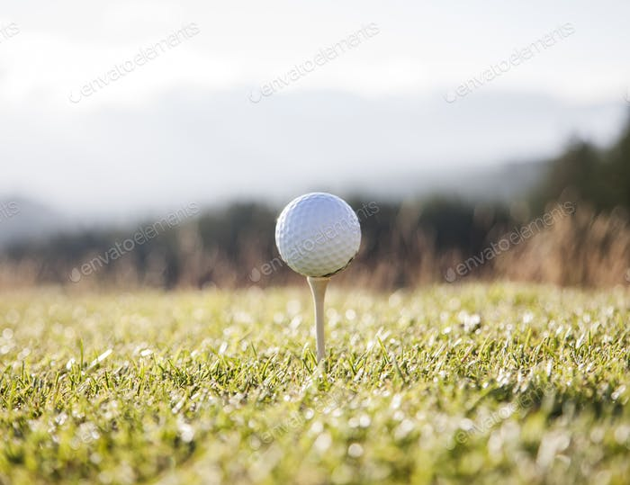 A golf ball on a tee ready to be hit.