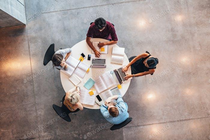 Junge Menschen, die gemeinsam um einen Tisch studieren