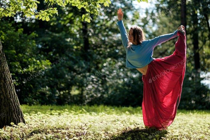 Sporty fit caucasian woman doing asana Virabhadrasana 2 Warrior pose posture in nature.