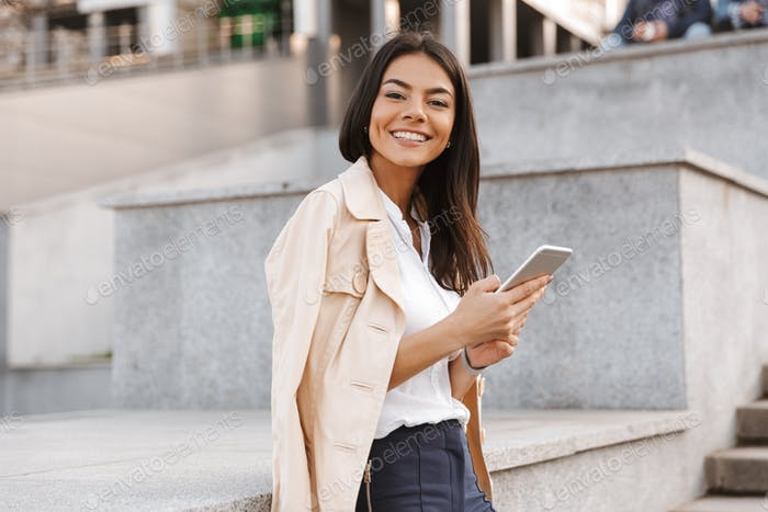 Cheerful young woman using mobile phone