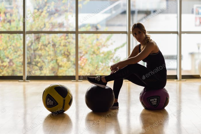 Woman sitting with fitballs in the gym.