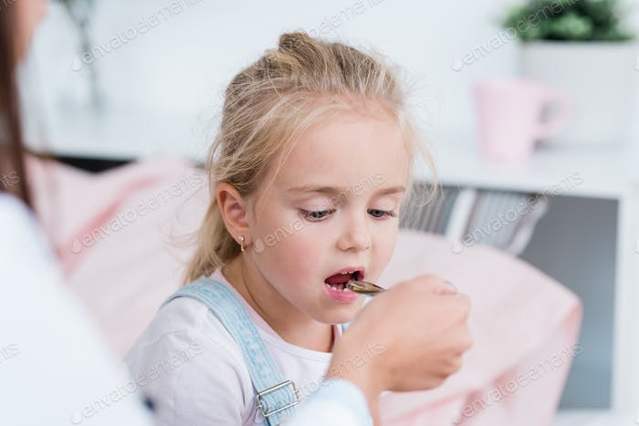Sick little blond girl taking medicine from spoon held by her doctor in hospital