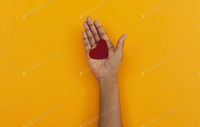 Rotes Filzherz in geöffneter Handfläche der schwarzen Frau