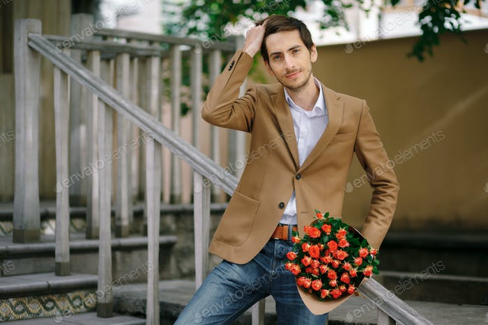 Man passes hand through his hair while holding bunch of roses