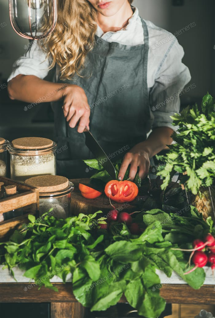 Woman cutting fresh ripe tomatoes on concrete kitchen counter