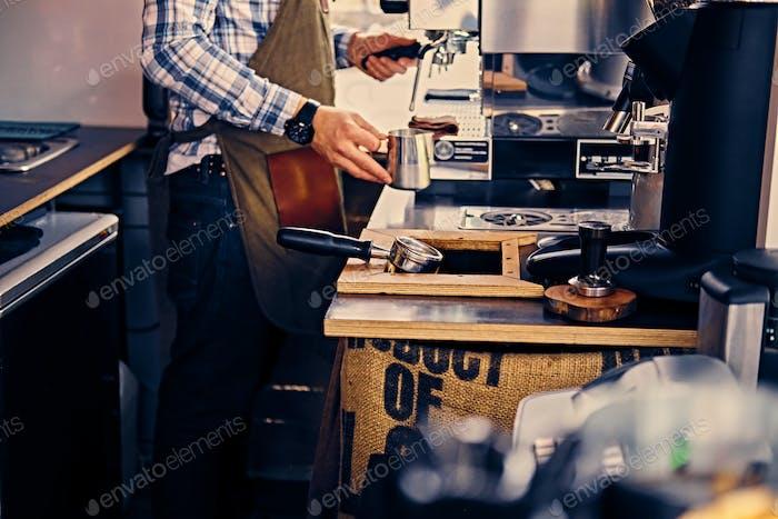 A man preparing cappuccino in a coffee shop.