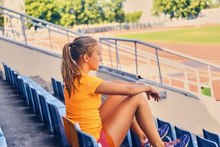 Блондинка спортивный женский бегун к быстрому старту позиции.