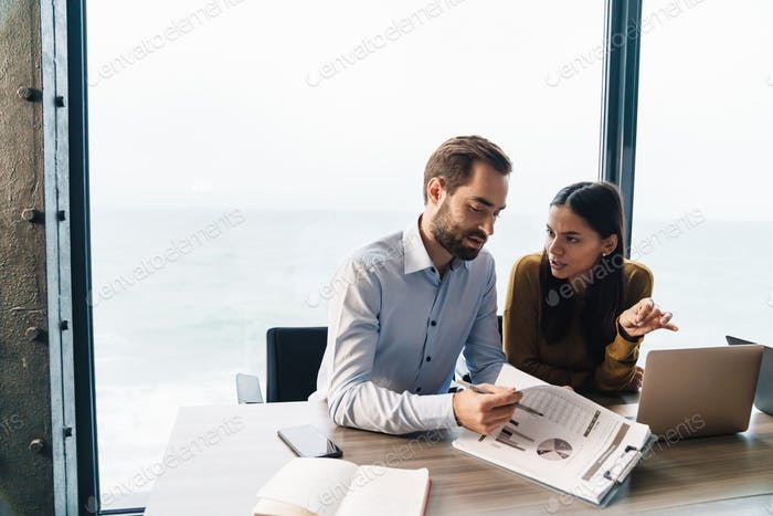 Image of confident young female and male colleagues working in office