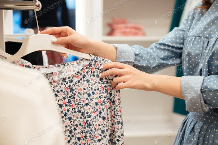 Cropped image of woman choosing dresses