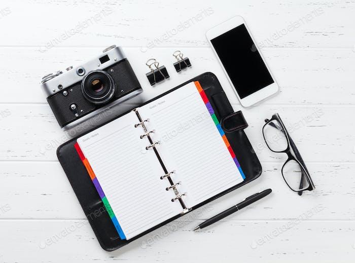 Kamera, Notizblock und Smartphone